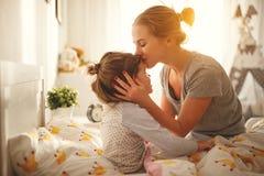 Modern vaknar hennes dotter i säng i morgon royaltyfri fotografi