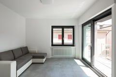 Modern vardagsrum i ny apartament med möblemang royaltyfri bild