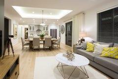 Modern vardagsrum inklusive soffor och tabeller bredvid kök royaltyfri foto
