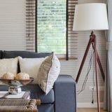 Modern vardagsrum med den svarta soffan och trälampan royaltyfri bild