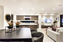 Modern vardagsrum med en television bredvid matställe och kök royaltyfri foto