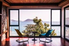 Modern vardagsrum med färgrik stol med golvet för havsikt till Arkivbilder