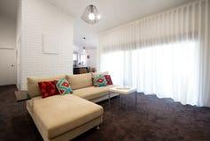 Modern vardagsrum med rena gardiner Fotografering för Bildbyråer