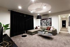 Modern vardagsrum med utrymme och hallet royaltyfri foto