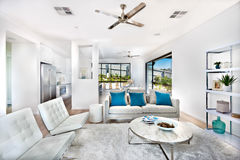 Modern vardagsrum med vita väggar som är upplysta med solljus Arkivfoton