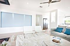 Modern vardagsrum och soffa bredvid ett kök arkivfoto