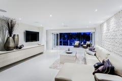 Modern vardagsrum på natten med soffor och kuddar royaltyfri foto
