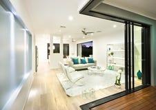 Modern vardagsrum som är upplyst på natten med ljus royaltyfria foton