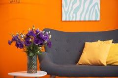 Modern vardagsruminre med den near färgväggen för bekväm soffa arkivbilder