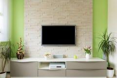 Modern vardagsruminre - tv monterade på tegelstenväggen med den svarta skärmen arkivbild