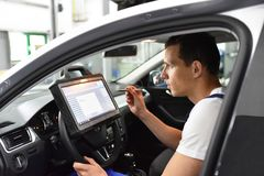 Modern vehicle diagnosis with computer in a garage - mechanic in. Spects and makes software update royalty free stock photos