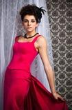 Modern victorian brunette model in red dress Stock Images