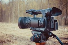 A modern video camera on a tripod against the forest stock photo