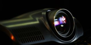 Modern Video projector. Video Projector playing in dark room stock photography