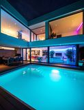 Modern villa with colored led lights at night. Nobody inside stock images
