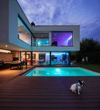 Modern villa with colored led lights at night. Nobody inside. Elle-shaped cube of a very modern house. Photograph taken at night or evening. The dog is well royalty free stock photos
