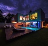 Modern villa with colored led lights at night. Nobody inside. Very modern house with lighted pool and wood around. The house is surrounded by nature in stock photos