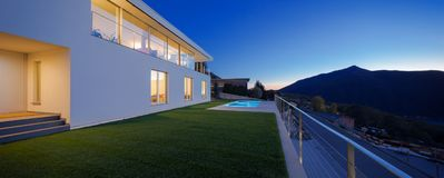 Modern villa, exterior in the night, lights on stock images