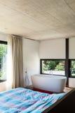 Modern villa, interior. Bedroom with bathtub Stock Photos