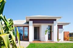 Modern villa med en gräsmatta nära ett långt bladträd och en blå himmel arkivbild