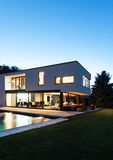 Modern villa by night. Modern villa with pool, view from garden, night scene stock images