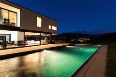 Modern villa, night scene. View from poolside royalty free stock photo