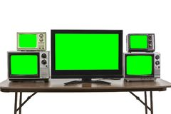 Five Televisions on Table Isolated on White with Chroma Green Sc Royalty Free Stock Images