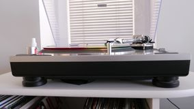Modern vinyl record player is near a window with blinds. On white nightstand, colorful vinyl record rotates on the turntable stock video footage