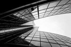 Modern and visionary skyscraper with many windows and reflection. S of clouds in the sky, black and white royalty free stock photo