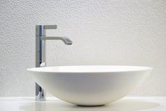 Modern vit badrumvask med vattenkranen royaltyfri fotografi