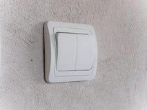 Modern vit ljus strömbrytare på den gråa betongväggen arkivfoto