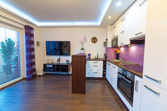 Modern vit vardagsrum med kök Arkivbild