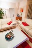 Modern vit vardagsrum med röda brytningar Arkivbild