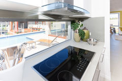Modern vitroceramic stove in the kitchen. Modern stove with vitroceramic tech besides spoons near the window in the kitchen, view of swimming pool through the Royalty Free Stock Images