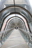 Modern Walkway, Paris, France. Modern glass walkway with three distant figures, Paris, France Stock Photos