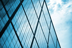 Modern wall made of glass and steel. With blue cloudy sky reflections royalty free stock photos
