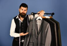 Modern wardrobe choice concept. Designer presents suit near clothes hangers. Man with beard royalty free stock photo