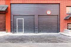 Modern warehouse building wall with closed metal gate Royalty Free Stock Images