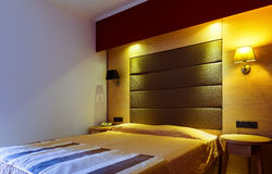 Modern, warm, inviting bedroom or hotel room. Light and shadows Royalty Free Stock Photo