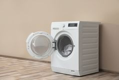 Modern washing machine with laundry near color wall. Space for text vector illustration