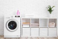 Modern washing machine near brick wall in laundry room stock photography