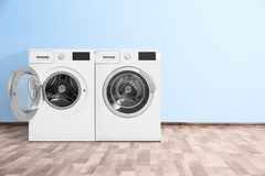 Modern Washing Machines Near Color Wall Indoors. Stock Image