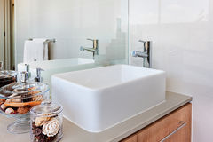 A modern washstand with faucet in front of the mirror in the was. A washroom of a luxury house including white washstand with silver faucet and natural herbal royalty free stock photo
