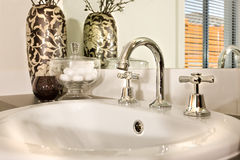 Modern washstand made in white ceramic with a curved faucet fixed to it seen as a close up view stock photos