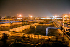Modern wastewater treatment plant of chemical factory at night. Water purification tanks stock photos
