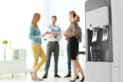 Modern water cooler with glass and blurred office employees on background. Space for text royalty free stock image