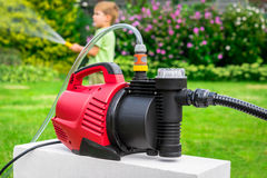 Modern water pump in garden on hot summer day Royalty Free Stock Photography
