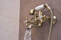 Modern water tap in the bathroom. Flowing water Stock Photos