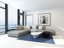 Modern waterfront apartment interior. With an upholstered grey corner lounge suite in front of floor-to-ceiling glass windows overlooking the ocean Royalty Free Stock Images