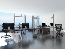 Modern waterfront office overlooking the sea. With several computer workstations on movable wheeled office tables in a bright airy room with a glass view window Stock Images